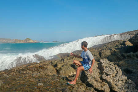 young man in a T-shirt and blue shorts sitting on a rocky shore. This is a view of man sitting on the rock by the sea