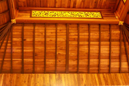 Wooden ceiling with golden elements in the Buddhist temple Brahma Vihara Arama, Bali, Indonesia. Balinese Wooden Ceiling at the House