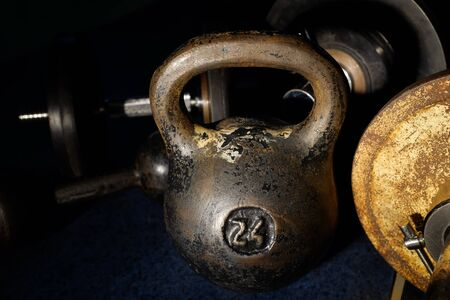 Old and heavy kettlebell weight in dark room. Banco de Imagens