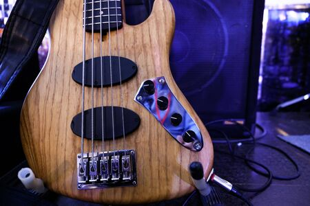 Electric bass guitar stands on the stage. Close up.