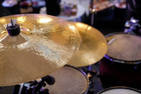 Close up of golden bronze cymbal plate part of drum set out of focus instrument parts in background Stock Photo