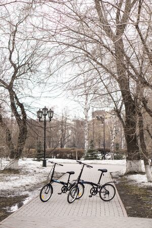 On the spring street of the city are bicycles. The snow hasn't melted on the lawns yet. Russia, Tyumen.