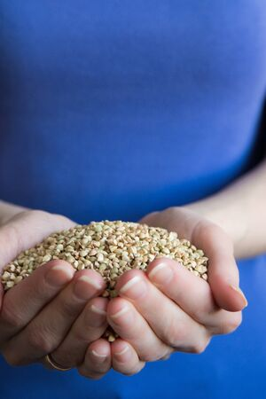 Concept handful green buckwheat grain in Woman hands front view Stock Photo - 128765170