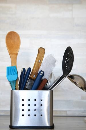 Kitchen Cutlery in metal stand with clean utensils on grey background