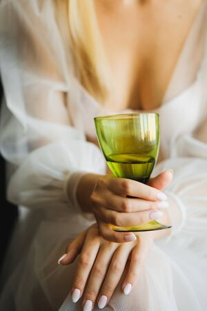 The bride holds a glass of champagne. Closeup. Wedding day,brides morning Stock Photo