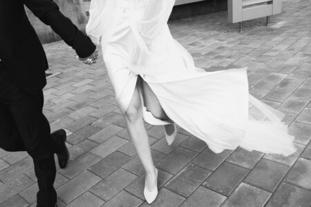 The bride and groom are on the sidewalk, legs close-up. Black and white. 版權商用圖片 - 128765535