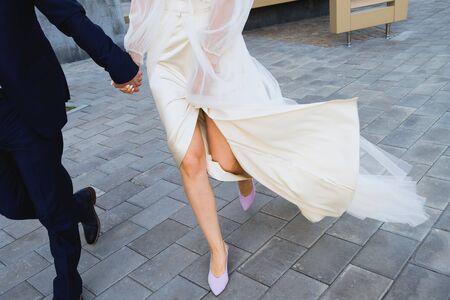 The bride and groom are on the sidewalk, legs close-up. 版權商用圖片