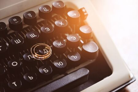 Wedding rings on the typewriter. Wedding rings placed on an ancient typewriter letter buttons. 版權商用圖片 - 128766364