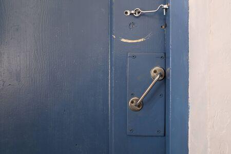 Old wooden entrance blue door with iron handle and lock. Horizontal shot. The door is hooked, the key. Shabby door.
