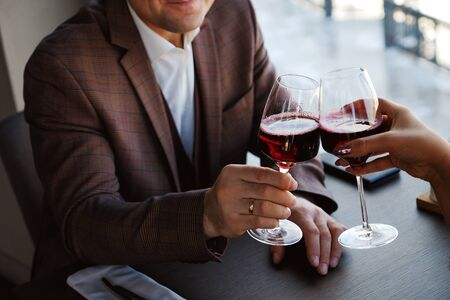 Two glasses of red wine juice. Romantic date in a cozy Italian restaurant. Man and woman clink glasses, hold . A date without alcohol. Life without alcohol. Healthy lifestyle. Banco de Imagens