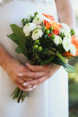 The bride is holding a beautiful white wedding bouquet. Close up.