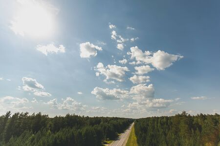 Aerial view of a free road, two-lane long forest road with tall green trees of dense forest growing on both sides. Beautiful blue sky with clouds on a Sunny day. Stock fotó