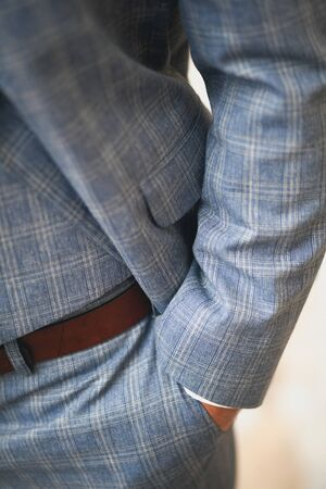 A mans hand in the pocket of stylish pants close-up. Successful young man, businessman, entrepreneur in expensive strict fashionable plaid blue suit, leather brown belt. Blurred background. 스톡 콘텐츠