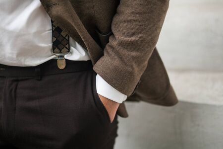 A mans hand in the pocket of brown stylish pants close-up on a white background. Successful young man, businessman, entrepreneur in an expensive business brown suit, white shirt and suspenders.