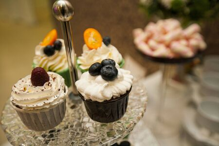 Vanilla cupcakes with cream icing, decorated with berries, close-up on a glass dish on the wedding table. The concept of food, confectionery.