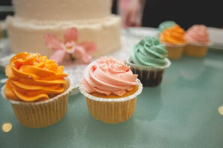 Vanilla cupcakes with bright cream glaze, close-up on a glass dish on the wedding table. Cake in the background, blur. The concept of food, confectionery.