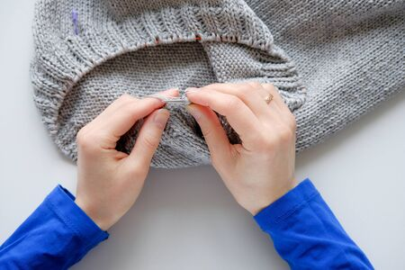 Unfinished knitting project in the hands of a young woman on a white background. The girl is knitting a woolen cloth. Imagens