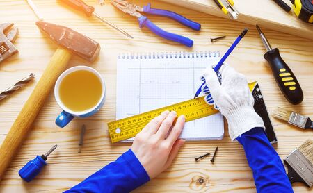 Carpenters hands make a drawing of the project for construction or repair, on a wooden table. Next to a mug of tea, construction tools. The workplace of the foreman. Home and professional repair.