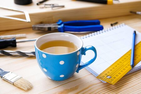 Mug of tea, drawings and construction tools for building a house or apartment renovation, on a wooden table. Snack or break in the workplace foreman or carpenter. Home and professional repair. Banco de Imagens