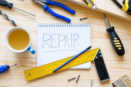 Notebook with the word repair, a mug of tea and tools for building a house or apartment repair, on a wooden table. The workplace of the foreman. The theme of home and professional repair, construction