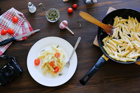 Italian pasta with sauce, cheese, tomatoes and spices on a white plate and in a pan on a wooden table. Nearby lies a fork, a knife, a towel, a camera. The concept of vegetarianism, food photography. Zdjęcie Seryjne