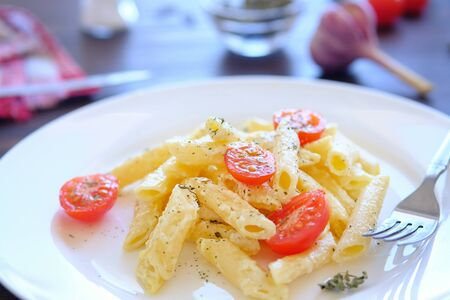 Italian pasta with cream sauce, cheese, sour cream, tomatoes and spices on a white plate on a wooden table. Lying next to a fork. The concept of healthy eating, vegetarianism. Blurred background Zdjęcie Seryjne