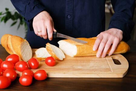 Hands of a woman or a cook cut with a knife a loaf of bread, a loaf or a baguette into slices on a wooden cutting Board. Near ripe tomatoes. Cooking organic natural farm food or Breakfast, homework. Stok Fotoğraf - 132063435