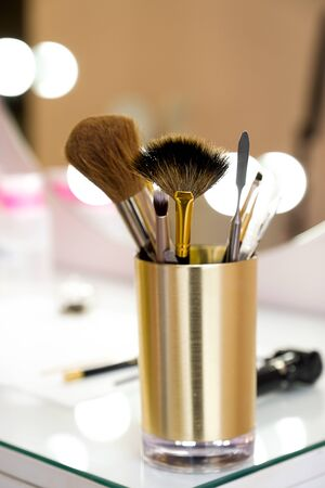 A set of makeup artist brushes for professional makeup on a white table in front of the mirror in the beauty salon, the Concept of cosmetology, modeling and correction of the eyebrow line, self-care. Stok Fotoğraf - 132063493