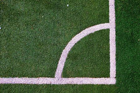 Part of the layout of the football field, the position of the corner kick. White marking lines on the green grass of the sports stadium.