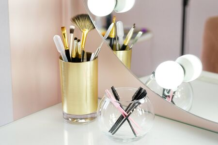A set of makeup artist brushes for professional makeup on a white table in front of the mirror in the beauty salon, the Concept of cosmetology, modeling and correction of the eyebrow line, self-care. Stok Fotoğraf - 132063492