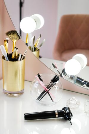 A set of makeup artist brushes for professional makeup and a mixer for mixing paint in front of a mirror in a beauty salon, the Concept of cosmetology, modeling and eyebrow correction, self-care. Stok Fotoğraf