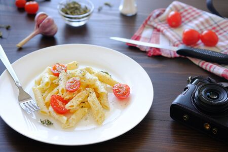 Italian pasta with cream sauce, cheese, sour cream, tomatoes and spices on a white plate on a wooden table. Nearby lies a fork, a knife, a camera. The concept of vegetarianism, food photography.