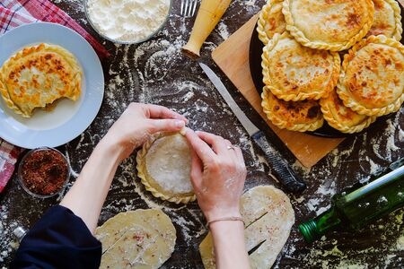 In the hands of the cook Georgian flat cake of raw dough on the background of a wooden table, sprinkled with flour. A woman cooks a pie or khachapuri. Near food, kitchen utensils. Home life.