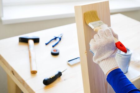 Repairman, carpenter, hired worker applies a protective varnish or paint brush on a wooden Board. Gloved hands, construction tools nearby. The concept of home and professional repair, construction.