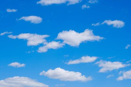 White clouds in a free idyllic blue sky on a Sunny summer day.