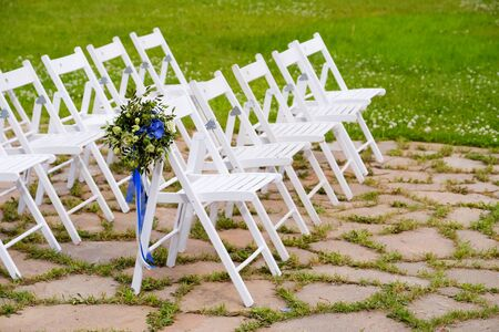 White wooden chairs decorated with flowers and bright satin ribbons, wedding decor at the ceremony. 스톡 콘텐츠