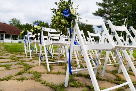 White wooden chairs decorated with flowers and bright satin ribbons, wedding decor at the ceremony in the pine forest