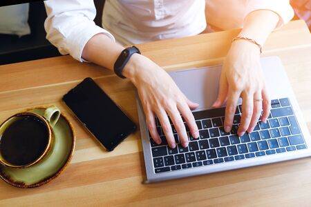 Female entrepreneur Manager using her laptop , working in a cafe or office. Near mobile phone and coffee. Freelance workplace, Breakfast business lady. Search for information on the Internet. Imagens