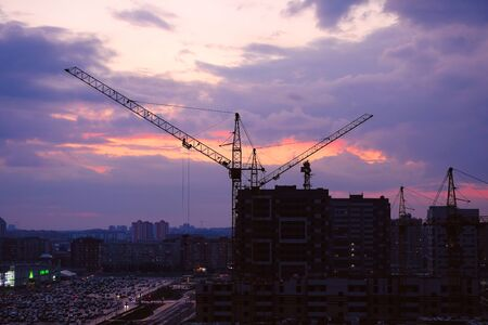 Tower crane, new buildings, Parking and cars in the distance during the sunset of the city, against the sky. Beautiful night city. Residential area with houses under construction.