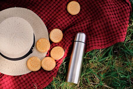 Summer picnic on a day off. Straw hat, cookies and flask on the rug or blanket. Selective focus