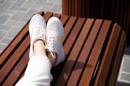 The girls legs in new white sneakers and jeans. A woman in sports shoes sitting on a wooden bench. Fashionable and stylish lifestyle. Stock Photo