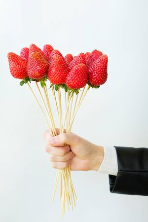 Alternative edible bouquet of berries in the hand of a man or woman, birthday, Valentines Day, holiday, close-up. Whole strawberry fruit on wooden skewers, on a white background. Selective focus.