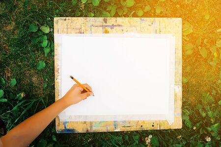 A child draws with a pencil on a white sheet of paper attached to a wooden Board stained with bright paint, lying on the green grass. The concept of creativity, hobby. Imagens