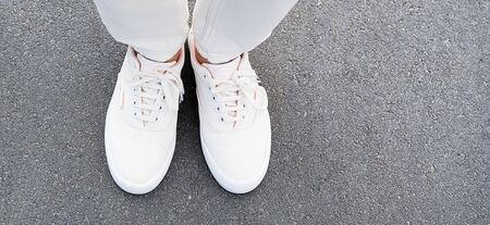 The girls feet in white jeans and sneakers on the sidewalk.