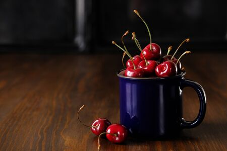 Cherry in a blue glass on a wooden table. Space for text.