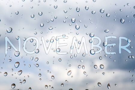 The word November and raindrops on the window glass against the clouds. The concept of rainy weather.