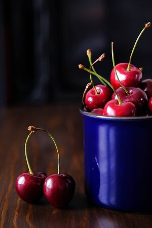 Ripe cherries in a blue glass and on the table. Selective focus. Stok Fotoğraf - 133141805