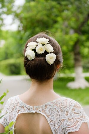 Flowers in the girls hair. Rear view of elegant blonde bride dressed in white dress, outdoors. The concept of the wedding. The day of the wedding, the brides morning.