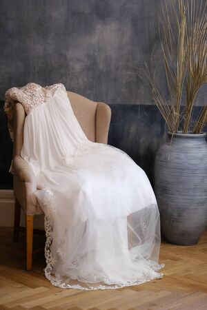 Wedding or evening dress and veil on beige chair. Beside blue vase with dry branches of the plant.