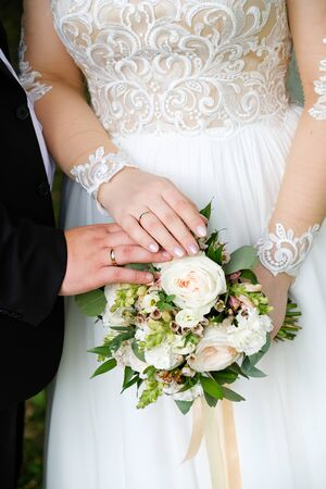 Young couple after wedding in Church, their hands gently touch. Wedding day, the bride holds a beautiful bouquet of white roses, peonies and green leaves. Wedding rings on the fingers of the newlyweds